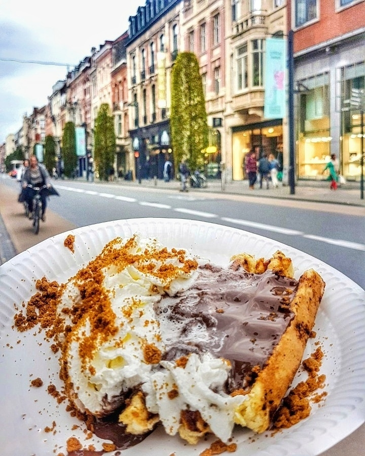 Belgium waffle topped with nutella and whipped cream with speculoos sprinkles, read more about what you can do in Leuven in 48 hours at www.whatsupcourtney.com #Leuven #travel #travelguide