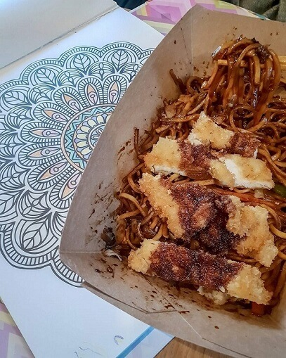 Adult colouring book and Ginger Katsu Chicken Noodles from Canaca World Street food restaurant in Newcastle Upon Tyne