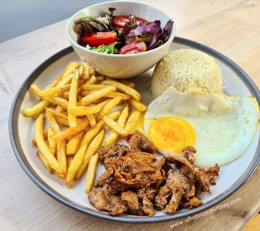 This is the Bifana on a plate, you get slices of marinated pork with a fried egg, salad and chips or rice at the Portuguese Cafe in Newcastle UK - www.whatsupcourtney.com