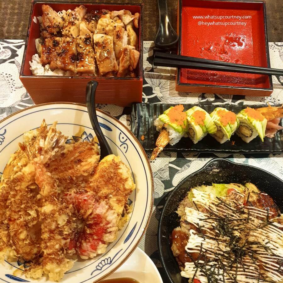 A table of Japanese food including Teriyaki chicken bento, a plate of sushi roll, Okonomiyaki and tempura rice, try this at Dojo  Japanese restaurant, one of the best places to eat in Newcastle Upon Tyne
