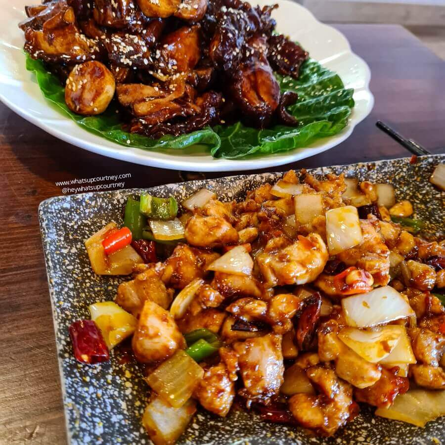 A plate of Kung pao Chicken and another plate of braised pork knuckle from Infusion 2018 Chinese restaurant in Newcastle Upon Tyne, one of the best places to eat in Newcastle